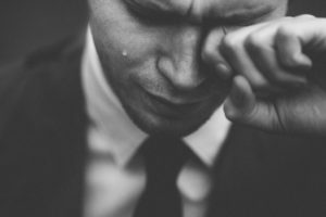 A man in a suit crying