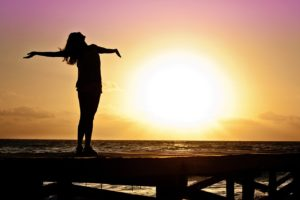 A woman with her arms stretched out against a sunset