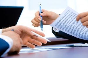 two peoples hands holding pen and paper