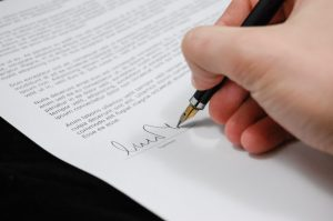 Someone signing their name on a contract