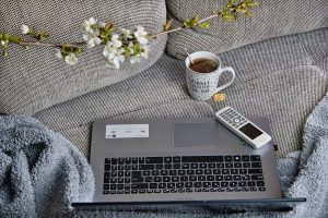 laptop on sofa next to cup of tea