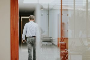 man walking away in office building holding phone