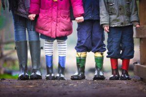 children standing in wellies holding hands